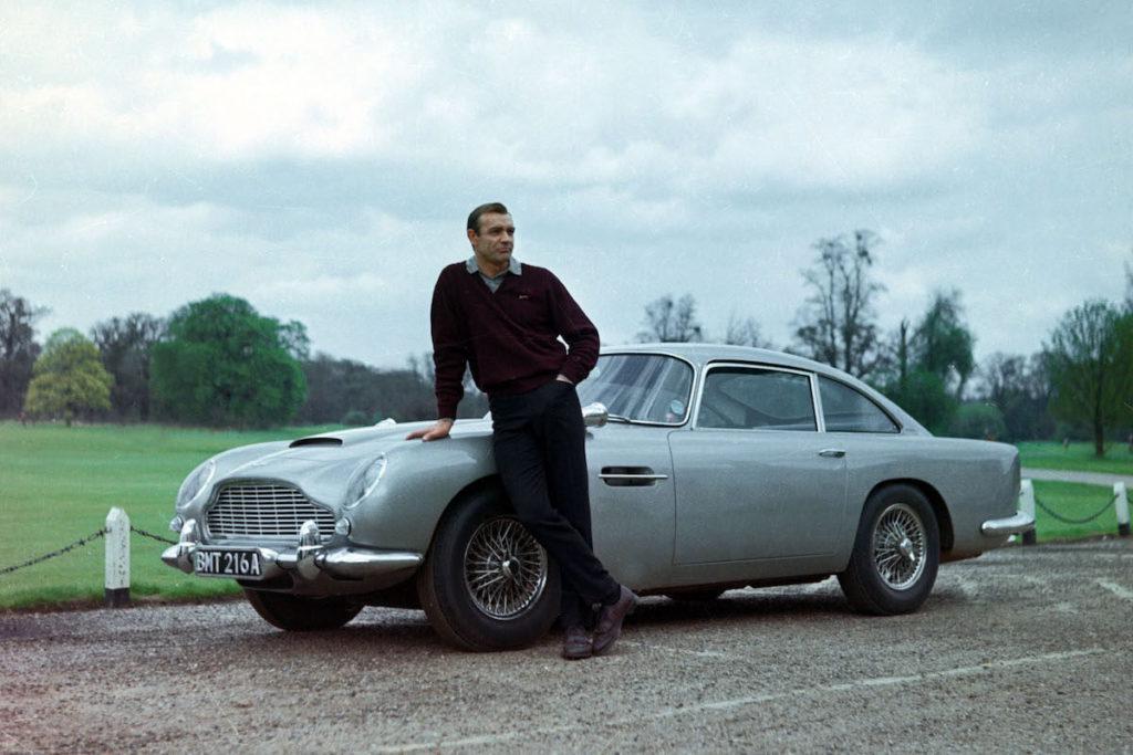 """Sean Connery posando junto con el Aston Martin DB5 de la película de James Bond """"Goldfinger""""."""