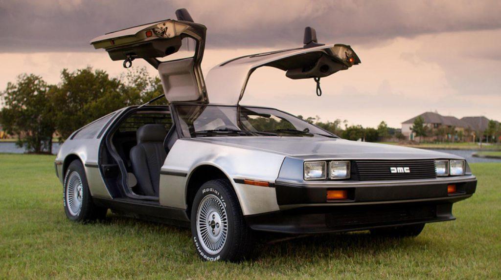 Imagen del DeLorean de la película Regreso al Futuro con las puertas abiertas. El coche está en la explanada de un campo.